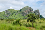 Rocky green mountain range with lush grass in foreground in landscape in northern Angola, Africa