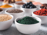 Spirulina powder in small white bowl and other superfoods on background. Selective focus. Different superfoods ingredients. Concept and illustration for superfood and detox food - 210017583