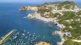 Aerial view of the beach and the small harbor of Cala Feola on the island of Ponza, in Italy. There are many boats and motorboats of tourists anchored in the bay and sheltered in the mountains. - 210020161