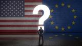 Geschäftsmann steht vor Wand mit den Flaggen von USA und EU und einem Fragezeichen