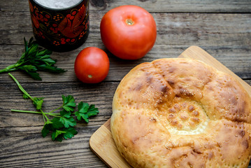 Bread cake and tomatoes on wooden background