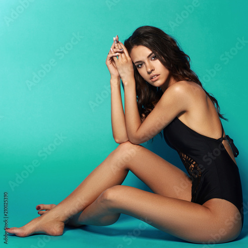932635619eb87 Young sexy slim tanned woman in black swimsuit posing and sitting on blue  background. Fashion