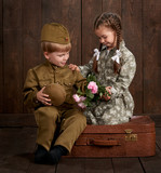children boy are dressed as soldier in retro military uniforms and girl in pink dress sitting on old suitcase, dark wood background, retro style - 210026332