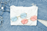 Multicolored sunglasses on a white T-shirt and jeans. Fashionable concept - 210026744