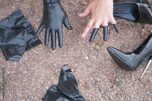 Two Hands In Torn Black Latex Gloves On Background Of Shoes Rocky Beach Top