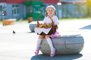 Little girl with a basket of bread. The girl holds a basket full of bread, rolls and flour products.
