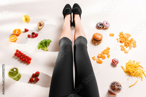 Athletic girl with healthy food on floor