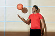 Black athlete in sportswear standing near wall in gym and throwing up basketball ball.