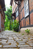 Low angle shot to a historical cobblestone alley with red half-timbered houses in the German medieval town Hitzacker. - 210042558