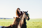 A girl sitting on a bay horse and the other horse approaching her. - 210051305