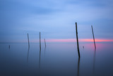 On the beach of Rockanje there are poles in the water for fishnets. This poles giving a beautiful subject for fineart photography. Photo taken during the blue hour just after sunset.