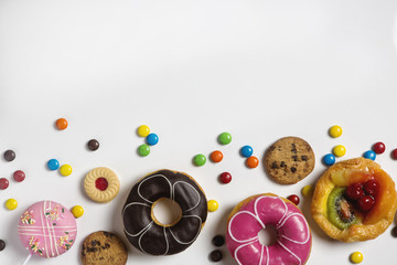 flat lay of dessert with candy, chocolate and strawberry donuts and fruitcake on white background
