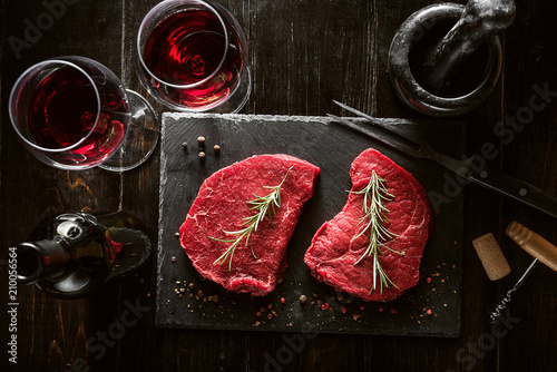 two pieces of fresh meat prepared for frying and wine with glasses on a wooden table - 210056564