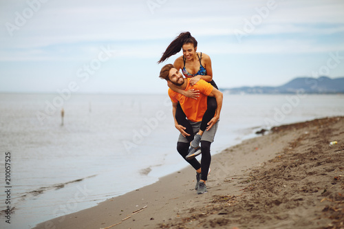 Young couple enjoying the beach after workout