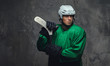 Hockey player wearing green protective gear and white helmet standing with the hockey stick on a gray background.
