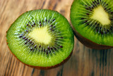Kiwi fruit cut into two pieces against a light background, close-up - 210072145