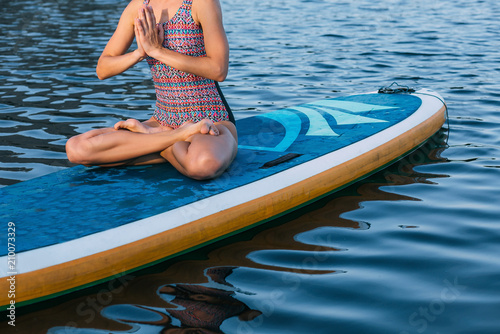 Fototapeta unrecognizable person meditating on paddle board. practice yoga on paddle board, woman sitting on paddle board Lotus Position