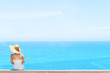 Elegant woman with white dress and white hat enjoys the view over the sea  summer concept