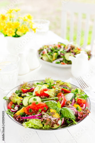 Foto Murales Fresh vegetarian vegetable salad with tomato, onion, cucumber, pepper, basil and lettuce. Salad on plate on white table