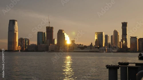 An evening sunset exterior establishing shot of the Jersey City skyline as seen from Pier 25 in Manhattan.