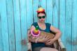 Eccentric slender woman with a hat, green shirtand glasses plays with funny red piglet in party dunce hat. Hands close-up. Copy space. 2019 Year Yellow Pig