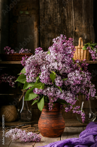 Foto Murales Bouquet of lilac flowers in a ceramic pot on old  table