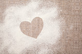 Concept of cooking with love. Heart drawn on wheat flour on the wooden table, next to it is confectionery inventory, with copy space - 210111515