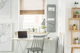 Front view of a desk with a laptop and lamp standing by the window, chair, wall organizer and shelves with cactus in a home office interior - 210111918