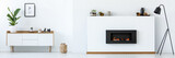 White room interior with fireplace, black metal lamp, cupboard with plants and decor, lantern on the floor and simple poster hanging on the wall