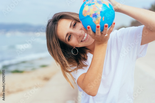 Foto Murales Happy excited woman holding up a world globe