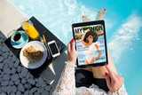 Woman relaxing by the pool and reading emagazine on tablet at breakfast. All contents are made up. - 210134325