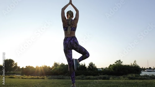 Plakat Woman practicing yoga outdoor at sunrise
