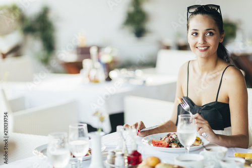 Attractive woman eating in restaurant - 210139754