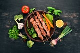 Baked Skewers of meat on a plate. On a wooden background. Top view. Copy space. - 210152123