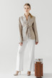 stylish woman in linen jacket standing near vintage suitcase isolated on grey background