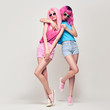Leinwanddruck Bild - Two Hipster Girls with Pink Fashion Hairstyle Hugging. Young Beautiful Pretty Model Woman in Stylish Trendy Summer Outfit. Cool Sisters Friends, Cheeky Emotion. Sweet colors
