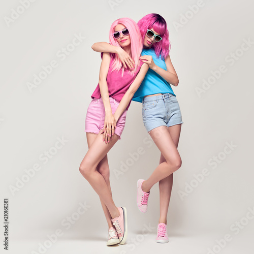 Leinwanddruck Bild Two Hipster Girls with Pink Fashion Hairstyle Hugging. Young Beautiful Pretty Model Woman in Stylish Trendy Summer Outfit. Cool Sisters Friends, Cheeky Emotion. Sweet colors