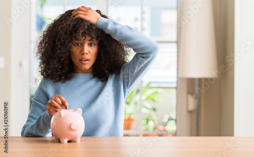 Leinwanddruck Bild African american woman saves money in piggy bank stressed with hand on head, shocked with shame and surprise face, angry and frustrated. Fear and upset for mistake.