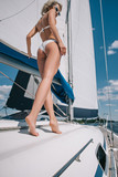low angle view of attractive young woman in bikini on yacht