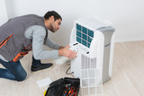 Man working on mobile air conditioning unit - 210178576