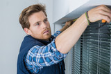 handyman installing a window shutter - 210178941