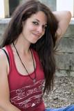 Portrait en extérieur d'une jeune femme brune aux cheveux longs - 210185100