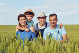Portrait of a happy family sitting on nature in the grass in summer. - 210185355