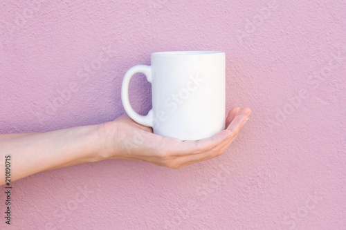 Young Caucasian Woman Holds on Hand Palm Blank Mockup White Mug on Light Pink Painted Wall. Airy Breezy Style. Template for Text Artwork Lettering. Trendy Minimalist Urban Atmosphere