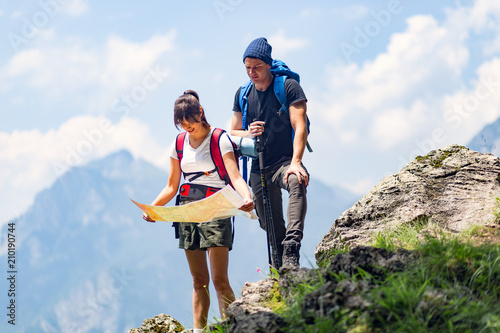 Couple hiking with map in mountains - 210190744