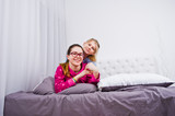 Two friends girls in pajamas having fun on bed at room. - 210192533