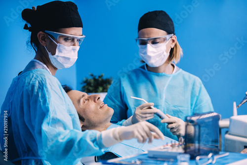 Dentists with a patient during a dental intervention - 210197934