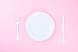 Concept minimal .Time to Eat.  Fork, knife and white Plate on a pink pastel Background. Top View. Flat Lay. Copy space for Text. - 210200168