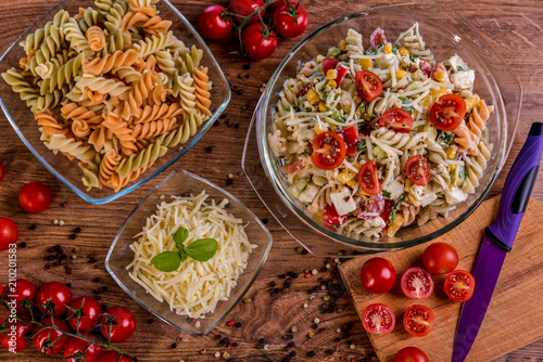 Delicious pasta salad or Mediterranean salad. Tomatoes mozzarella basil corn spice and olive oil on a wooden table. Traditional Italian food - 210201583