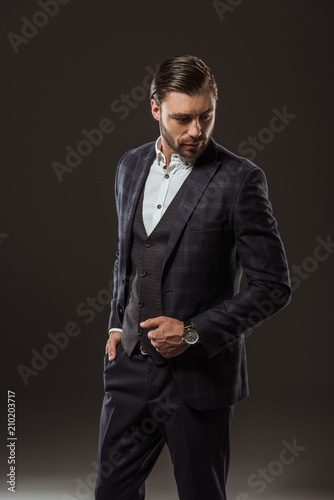 Fototapeta handsome stylish young man in suit looking down on black